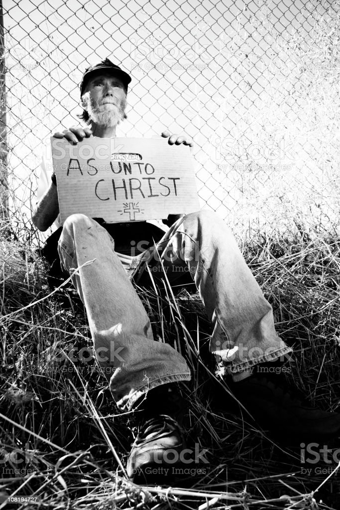 Homeless Man Holding Sign 'As Unto Christ', Black and White royalty-free stock photo