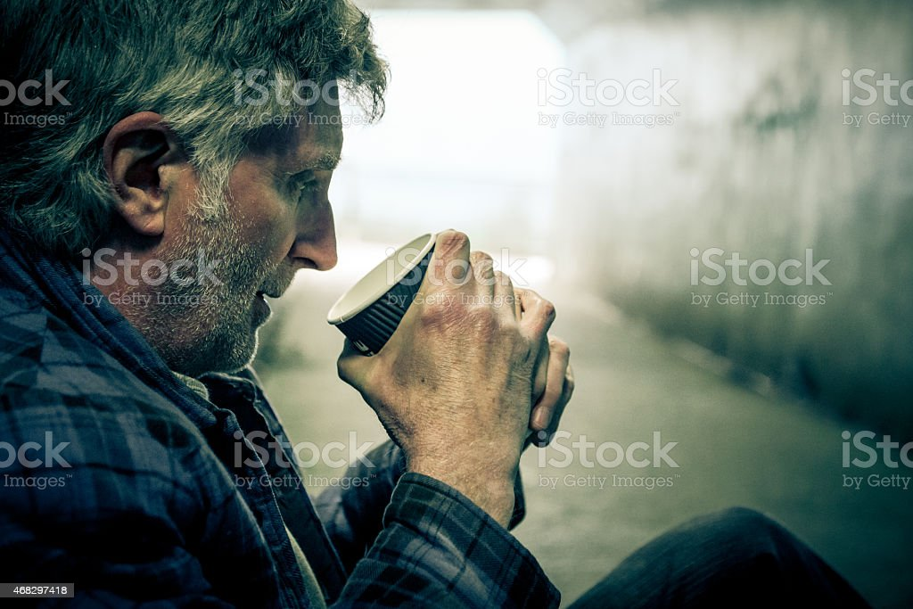 Homeless man in subway tunnel drinking from paper cup stock photo