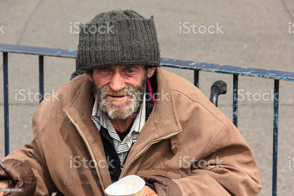 Homeless man in wheelchair holding paper cup stock photo