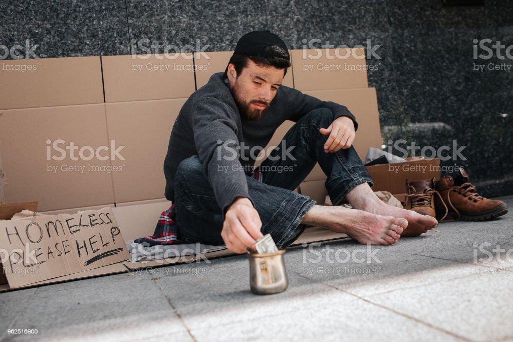 Mendigo é sentado no papelão copo metal exterior e alcançar com a mão. Ele chega a um dólar. Há um sinal diz desabrigados por favor me ajude. Cara quer levar esse dinheiro - Foto de stock de Adulto royalty-free