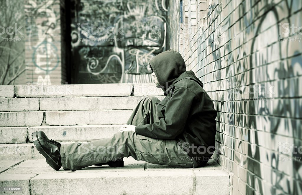Homeless man leaning against a graffiti-covered wall royalty-free stock photo