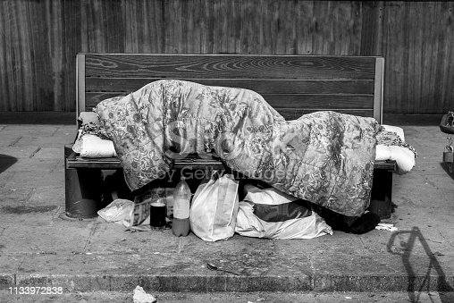 istock Homeless man, Poor homeless man or refugee sleeping on the wooden bench on the urban street in the city covered with a blanket with bags of clothes and junk on sunny cold day, social documentary concept 1133972838