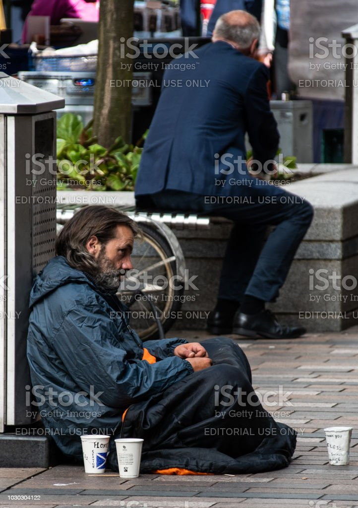 A homeless man sits in Murray Street whilst a business man turns his back to drink coffee stock photo