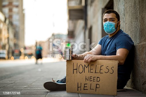 Young homeless man sitting and asking for help while holding donation can and