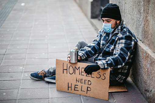 Homeless young man sitting on sidewalk and begging alone. He is wearing protective face mask and holding out a can and begging for money. His head is bowed in shame and tiredness and hunger.