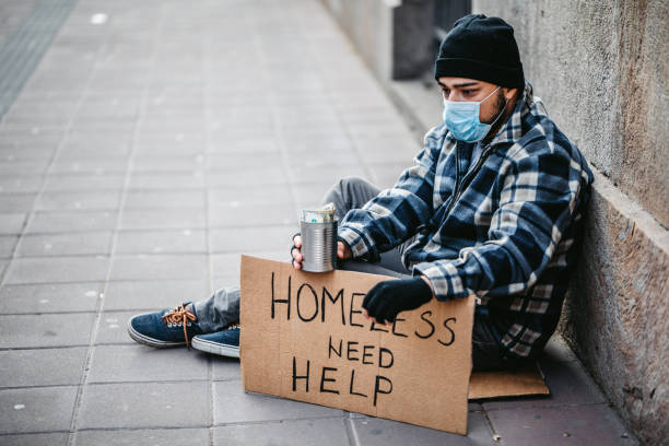 Homeless man sitting and begging for help Homeless young man sitting on sidewalk and begging alone. He is wearing protective face mask and holding out a can and begging for money. His head is bowed in shame and tiredness and hunger. homelessness stock pictures, royalty-free photos & images