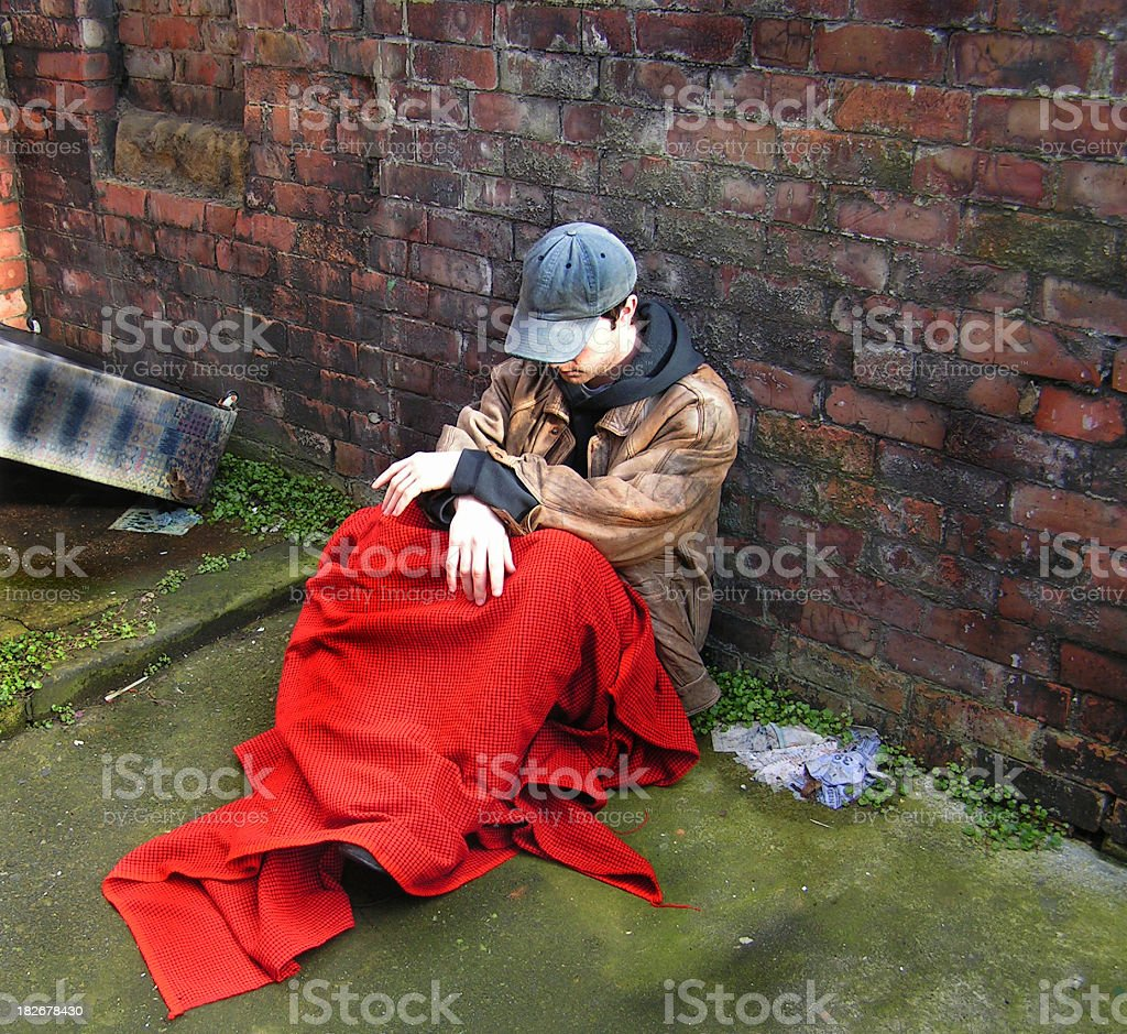 Homeless man sitting by a brick wall under a red blanket stock photo