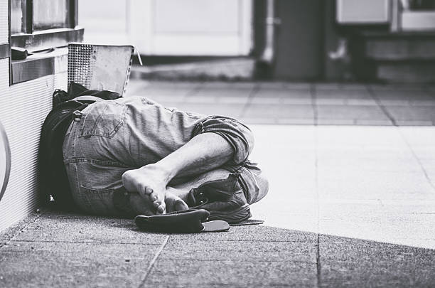 homeless man sleep on the street - homelessness stock photos and pictures