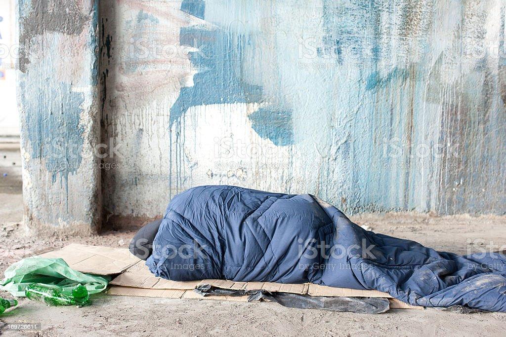 Desalojados homem dormindo em saco de dormir de papelão - foto de acervo