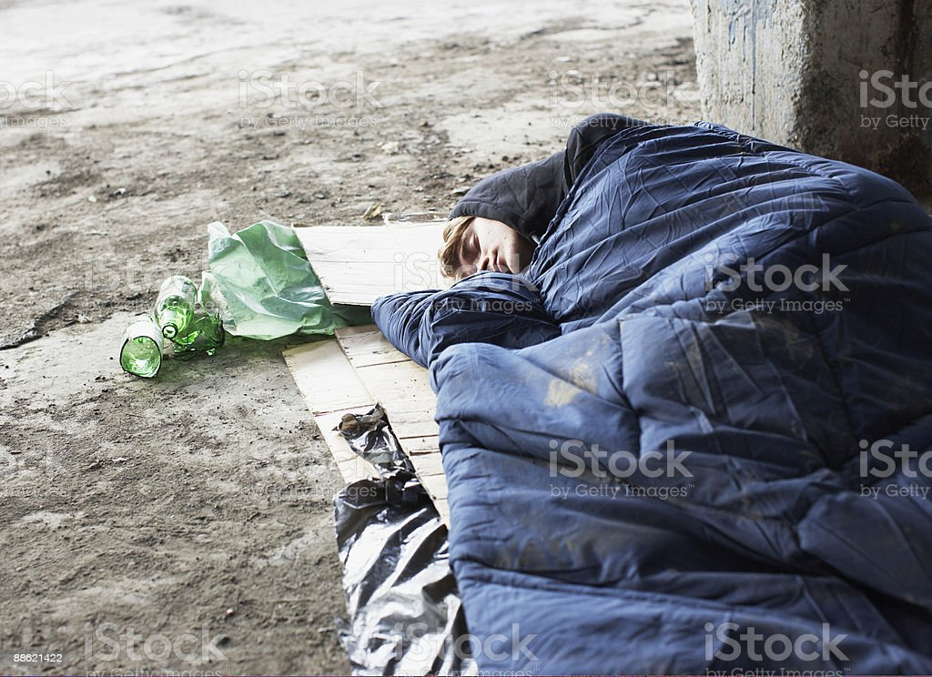 Homeless man sleeping in sleeping bag on cardboard stock photo