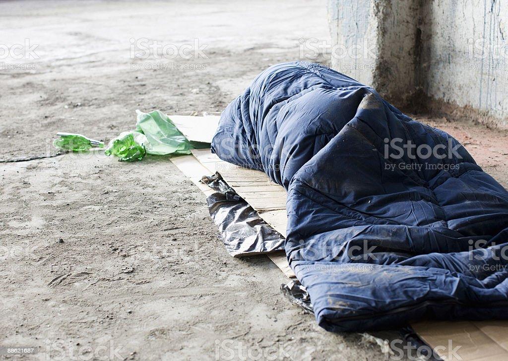 Homeless man sleeping in sleeping bag on cardboard stock photo
