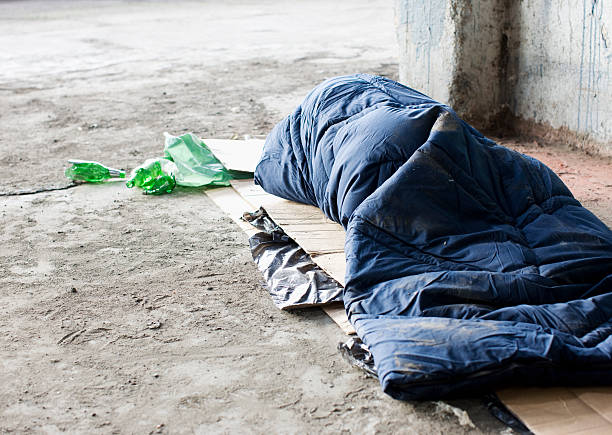 homeless man sleeping in sleeping bag on cardboard - homelessness stock photos and pictures