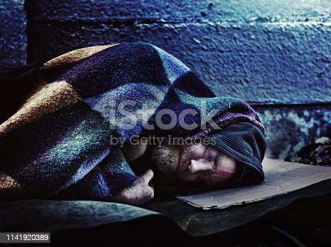 A homeless man sleeps under a ratty blanket on a hard stone sidewalk