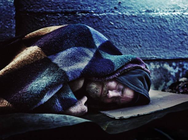 hemlös man sova på trottoaren - cold street bildbanksfoton och bilder