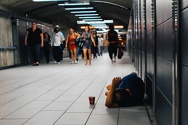 Homeless man sleeping on the floor Montreal metro