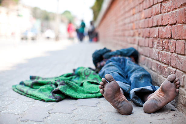 Homeless man sleeping on the sidewalk stock photo
