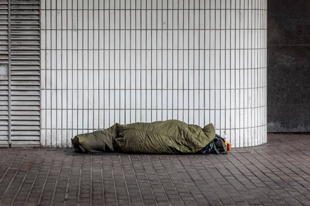 Homeless man sleeping outside Euston Station stock photo