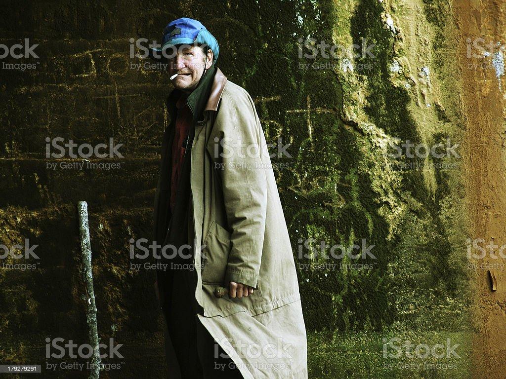 Homeless Man Smoking Under the Bridge with Walking Stick royalty-free stock photo