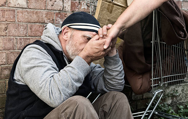 homeless man taking a woman's hand - homelessness stock photos and pictures