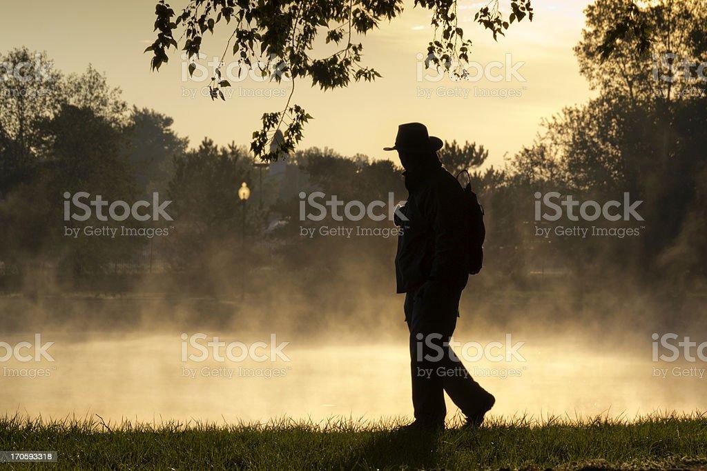 Homeless man walks along foggy lake on cold fall morning stock photo