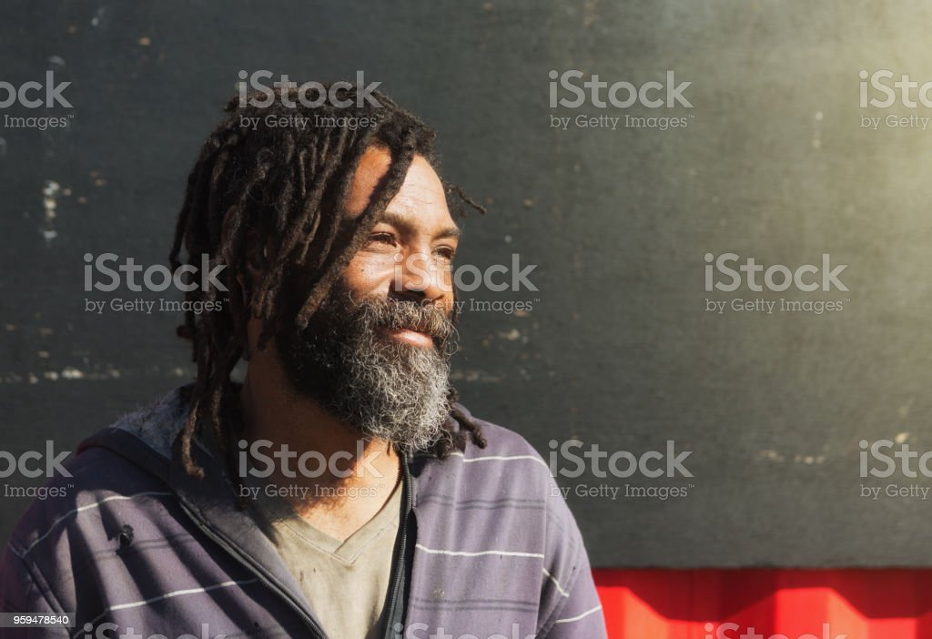 Homeless man with dreadlocks and beard smiles wistfully stock photo