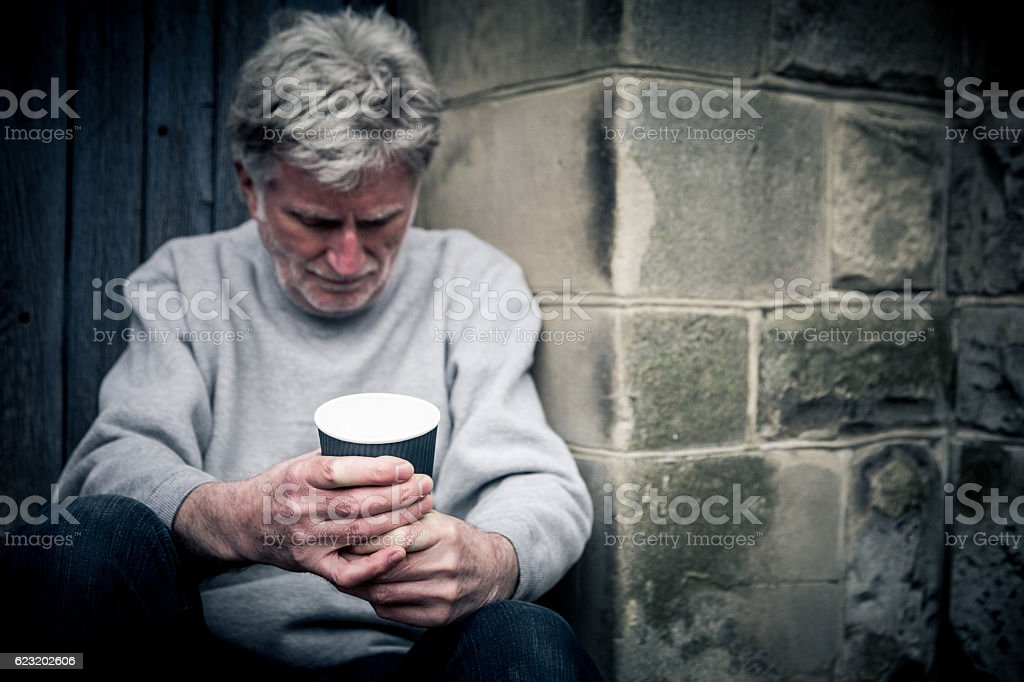 Homeless man with gray hair and stubble in wooden doorway stock photo
