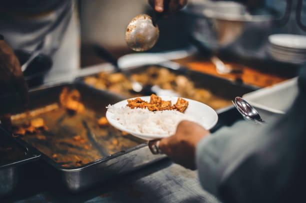 Obdachlose erhalten kostenlose Wohltätigkeitsnahrung aus den Händen von Freiwilligen: Konzept der Hungerprobleme in einer helfenden Gesellschaft – Foto