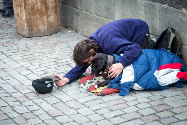 Homeless person begging for money on bridge in city Prague, Czech Republic - 30 November, 2018: color image depicting a homeless man on his knees and begging for money on the Charles Bridge in Prague, Czech Republic in the middle of winter. People and tourists walk past the homeless man, apparently oblivious and not noticing him. Room for copy space. face down stock pictures, royalty-free photos & images