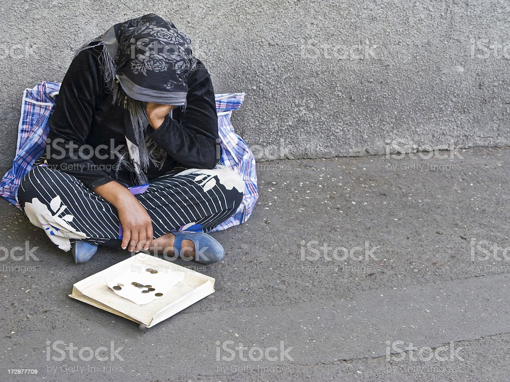 Homeless person sitting on the street stock photo