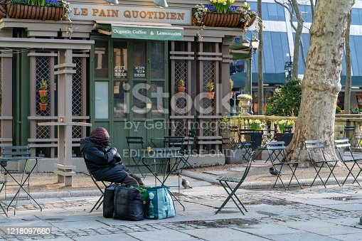 Manhattan, New York, April 6, 2020: A homeless person sleeping in Bryant Park abandoned because of the COVID-19 pandemic. Homeless people lost all income and life support in the deserted city.