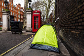 Color image depicting a small tent on the pavement of the city street in London, UK, with a homeless person sleeping inside. Room for copy space.