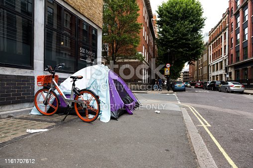 London, UK - 6 July, 2019: Color image depicting a small tent on the pavement of the city street in London, UK, with a homeless person sleeping inside. Room for copy space.
