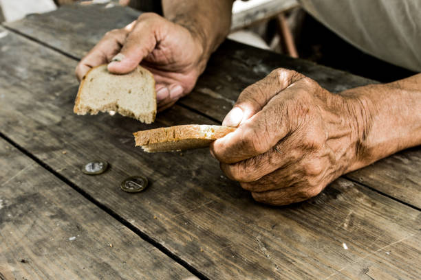 Homeless. Poverty in retirement. Hands the poor old man's, piece of bread and change, pennies on wood background. The concept of hunger or poverty. Selective focus. stock photo