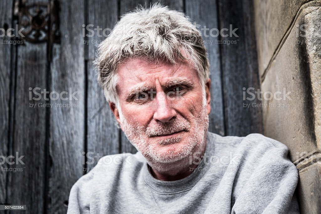 Homeless senior adult man sitting and begging in doorway stock photo