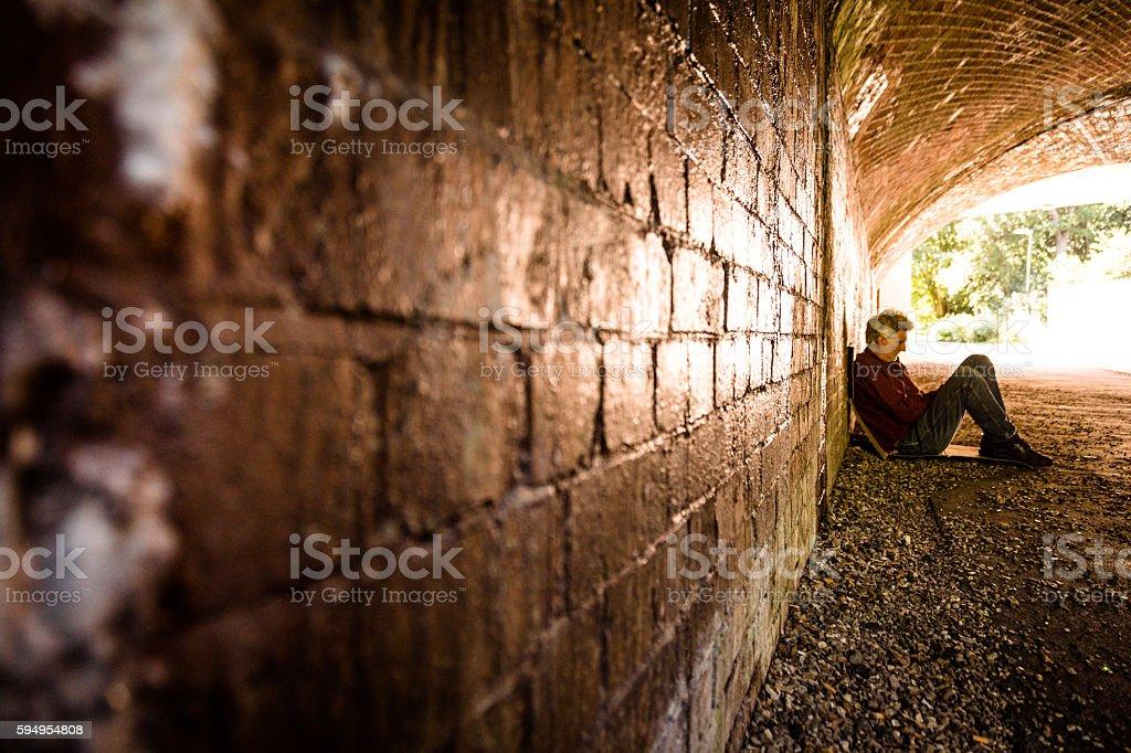 Desalojados senior adulto homem sentado e implorando no metrô, Túnel - foto de acervo