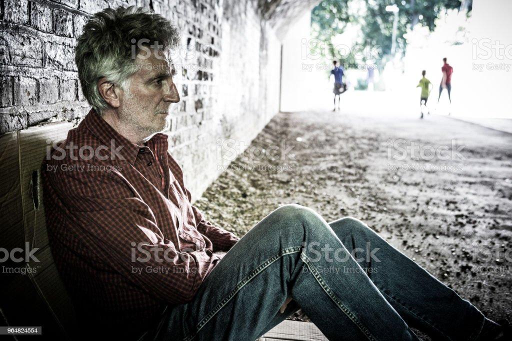 Homeless senior male sleeping rough in dark subway tunnel royalty-free stock photo