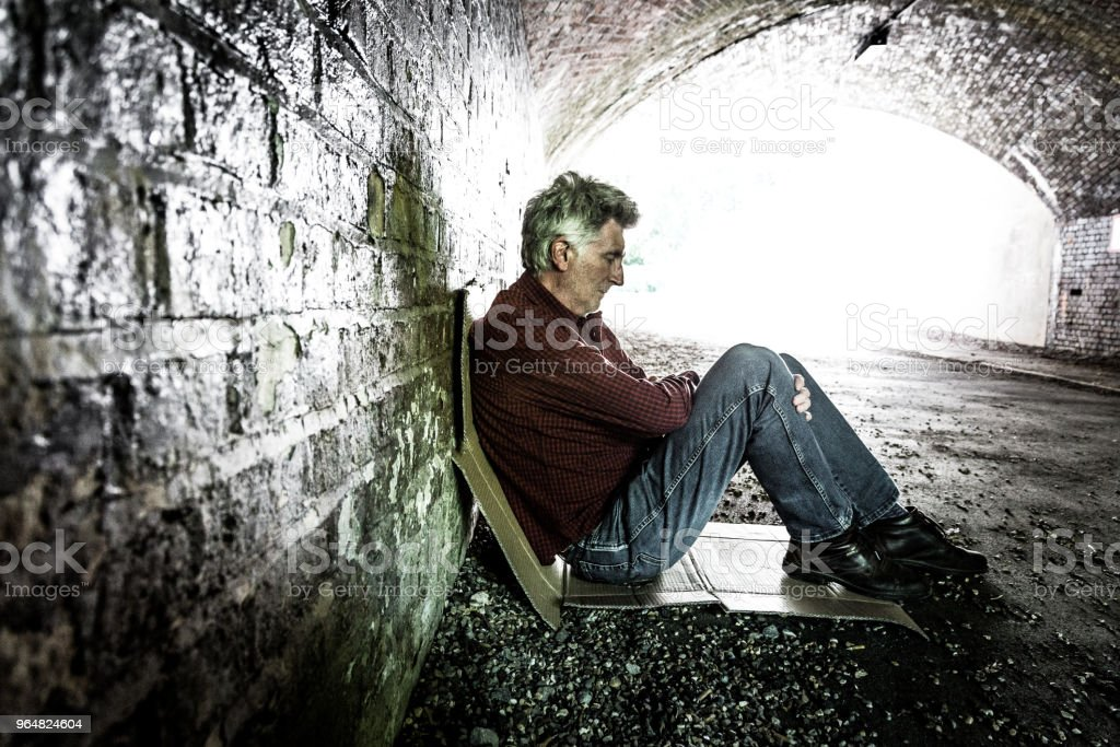 Homeless senior male sleeping rough in dark subway tunnel royalty-free stock photo
