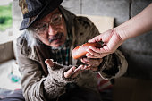 istock Homeless senior man with gray beard sitting hungry and beggar from people walking street. 1301869299