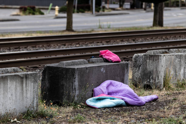 Homeless sleeping bag next to an old railroad track concrete block stock photo