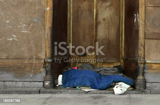 A homeless women sleeping in the entrance of an abondoned building.