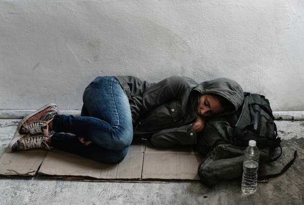 homeless sleeping on the sidewalk - homelessness stock photos and pictures