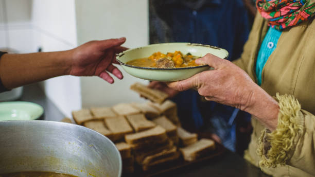 Homeless Soup kitchen food handouts to the poor stock photo