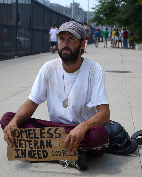 Homeless veteran pauses as he begs for money stock photo