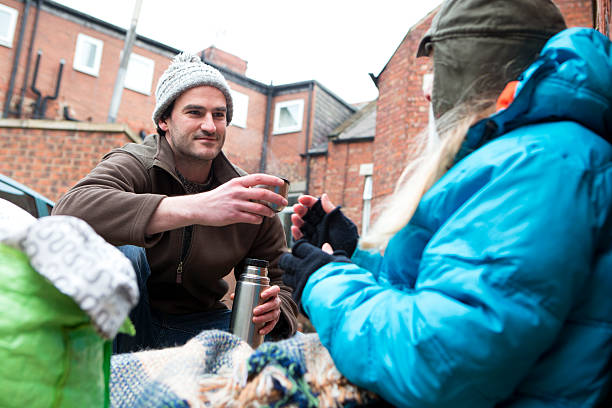 homeless woman receiving help - homelessness stock photos and pictures