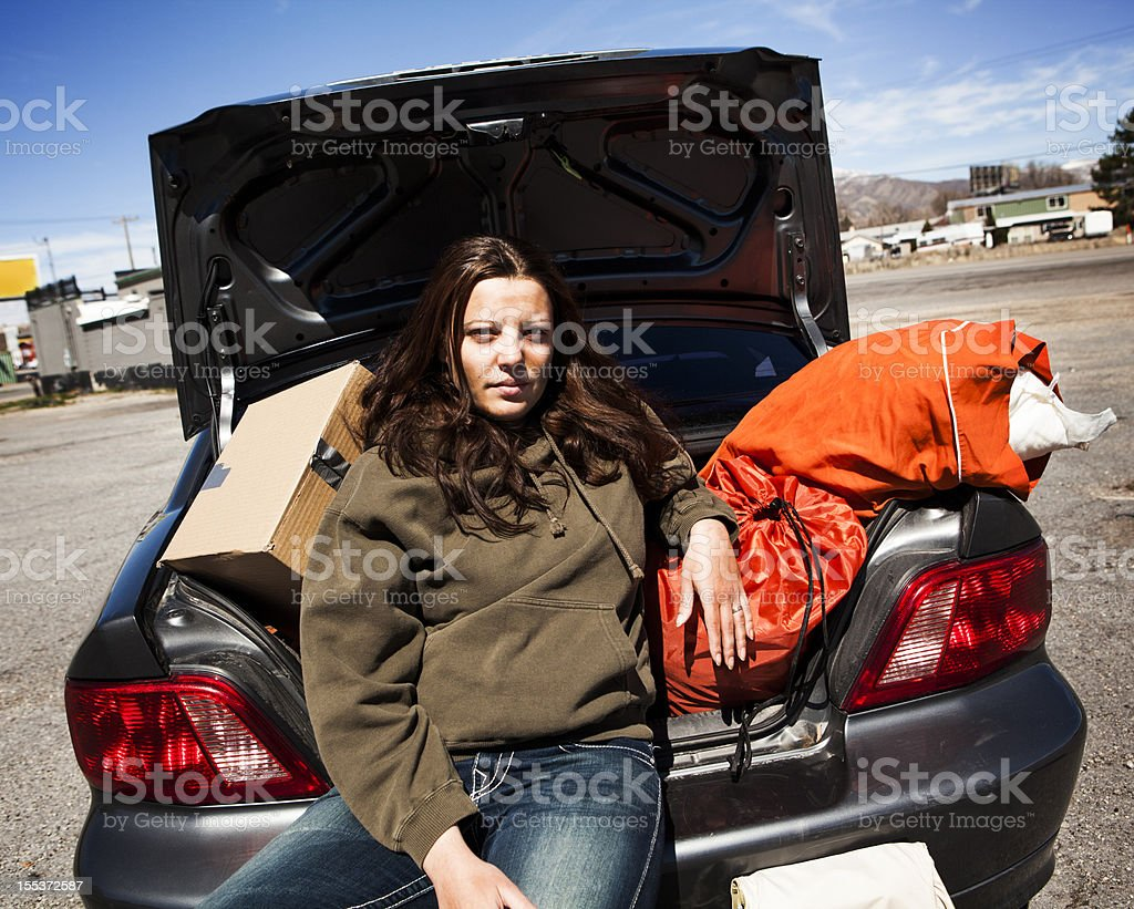 Homeless Woman Sitting in Back of Car with Belongings stock photo