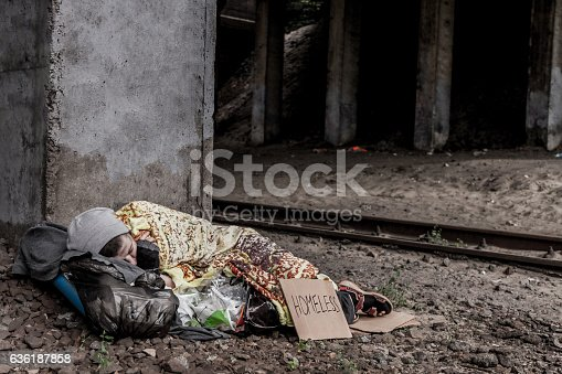 Homeless woman with sign sleeping under the bridge near the rail track