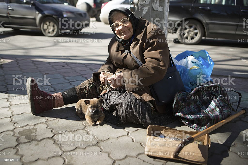 Homeless woman with little dog in center of Chisinau Moldova stock photo