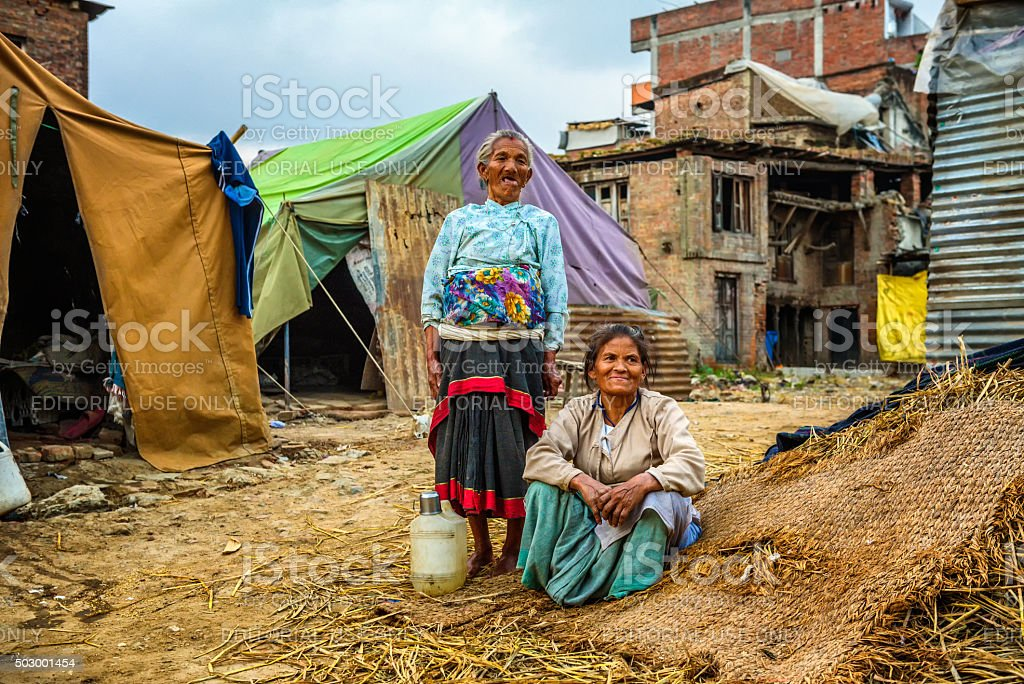 Homeless women sit in front of their tent in Nepal stock photo