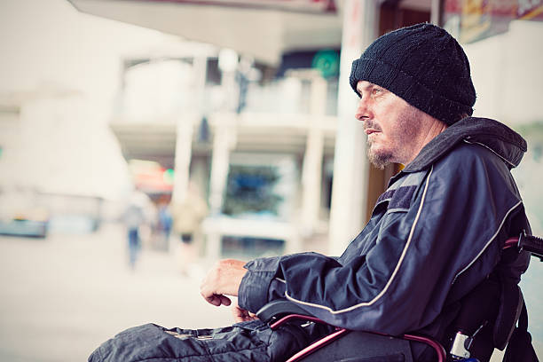 Homeless young invalid man sitting in wheelchair on the street stock photo
