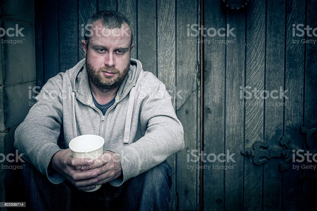 Homeless young man sitting in front of wooden door stock photo